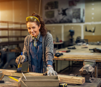 Portrait view of happy attractive hardworking middle aged professional female worker painting wood with black colour in the sunny workshop or garage.
