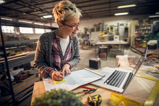 Close up view of charming smiling motivated short hair attractive middle aged industrial female engineer with eyeglasses working with blueprints and laptop in the workshop.
