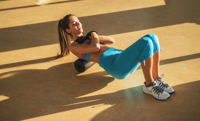 Attractive motivated focused young slim fitness girl doing exercises while lying on foam roller in the sunny gym.
