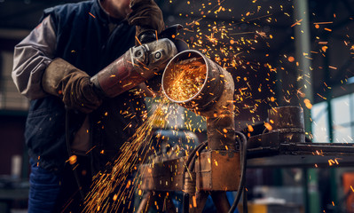 Side close up view of professional focused worker man in uniform working on the metal pipe sculpture with an electric grinder while sparks flying in the industrial fabric workshop.