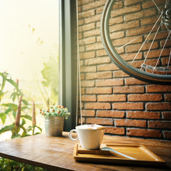 A cup of hot latte coffee on a wooden table. A stylish modern cafe with wooden tables and a brick wall with a bicycle.