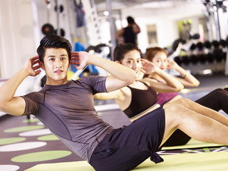 young asian people exercising in gym