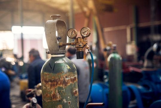 Close up focus view of welding equipment. Acetylene gas cylinder tank with gauge regulators manometers in the industrial fabric workshop.