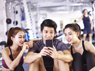 young asian adults looking at cellphone in gym