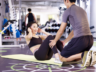 young asian couple exercising in gym