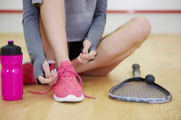 Unrecognizable woman tying sports shoe at court