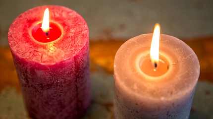 two burning candles on wooden table