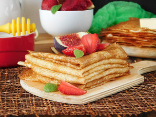 A pile of crepes decorated with a strawberry and a fig. Breakfast on a wooden background