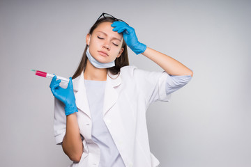 Young tired woman doctor with a syringe in her hand, headache