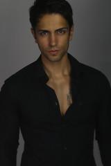 Bel homme brun portant une chemise noir