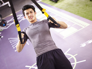 young asian adult working out in gym using straps.