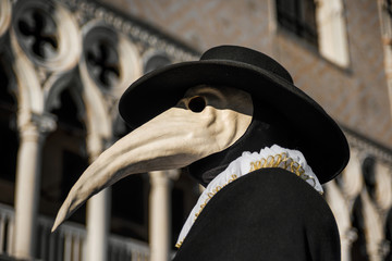 Photo sur Toile Europe Centrale Plague Doctor Mask, traditional venetian costume of Venice Carnival, with Doge Palace gothic decoration in the background