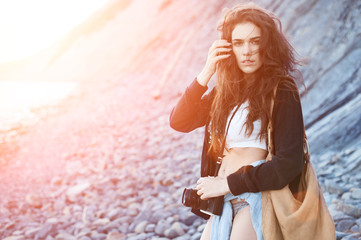 Girl in style of boho with a camera at sea in the rays of a bright sun