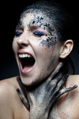 Young girl with creative makeup with texture. Beautiful model with sparkles. Trendy purple smokies. Beauty of face, shining skin. Emotions with scream. Photo is taken in the studio.