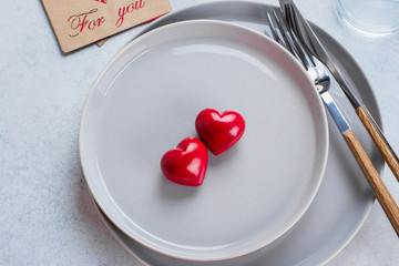 Valentine's day background table setting with two ceramic hearts on plate. Top view, copy space