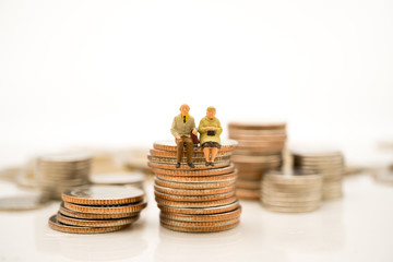 Miniature people, elderly people sitting on stack coins using as job retirement and insurance concept