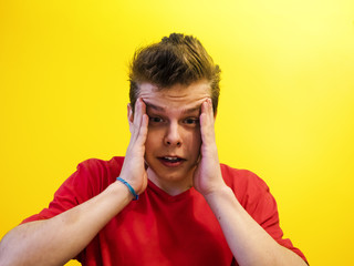 Portrait of a young man with a shocked facial expression isolated on a yellow background