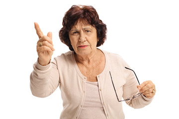 Angry elderly woman scolding someone and gesturing with her finger