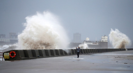 A walker takes a photo of the sea in New Brighton, on the coast of the Wirral Peninsula