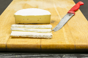 Camembert cheese on a chopping board.