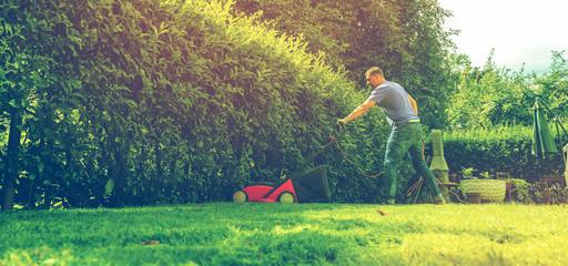Mann mit rasenmäher im eigenen garten (Gartenpflege)