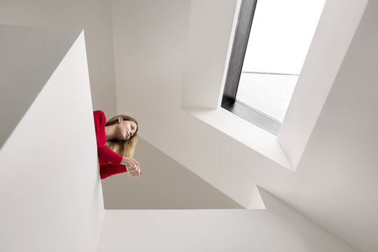 Young woman on upper floor under roof window
