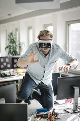 Businessman wearing VR glasses in office pretending to be a lion