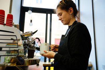 Hipster female barista enjoying working process preparing coffee drinks using professional equipment in cafeteria. Woman waitress in apron steaming milk on machine making cappuccino