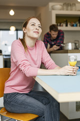 Smiling young woman with glass of orange juice in kitchen at home with man in background
