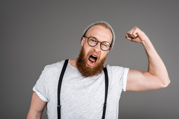 excited bearded man showing biceps and screaming at camera isolated on grey