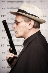 Dangerous criminal man portraited with silenced pistol in front of mug board