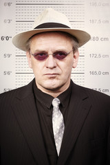 Bad criminal man in sunglasses and hat in front of mug board