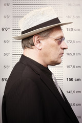 Criminal man in sunglasses and hat in front of mug board