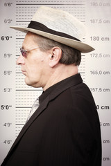 Criminal man portraited in sunglasses and hat in front of mug board