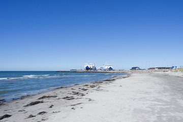Laesoe / Denmark: View over the beautiful sand beach to the ferry terminal in Vesteroe Havn