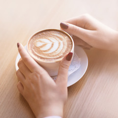 Woman holding cup of capuccino on wooden table.