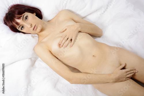 Frau liegt zur Erholung und Entspannung nackt im Bett von ...