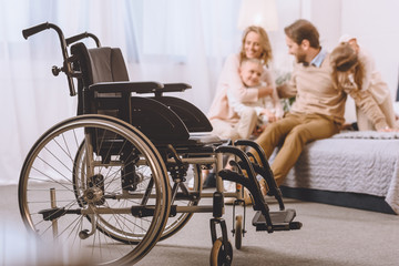 happy father with disability and mother sitting with children on bed with wheelchair on foreground