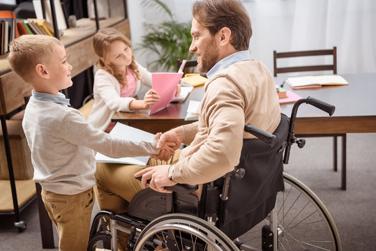 happy father on wheelchair and son shaking hands