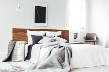 Black poster above wooden bed