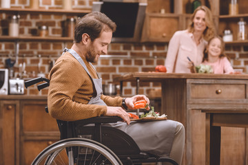 side view of smiling man in wheelchair cutting vegetables for salad while happy mother and daughter standing behind