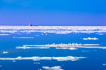 Ice floes and lighthouse along the shores of Prince Edward Island, Canada.