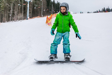 Cute child girl is snowboarding on the snow mountain