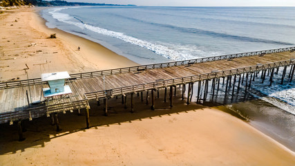 Drone view of a pontoon with a lifeguard tower along with waves hitting the beach underneath