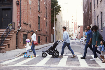 Two families with daughters crossing road
