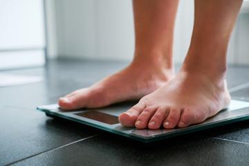 Female bare feet on the digital scale in the bathroom