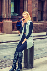 Eastern European Professional Woman working in New York, dressing in long vest, black fitted T shirt, pants, long leather boots, sitting on vintage street, listening cell phone. Filtered effect..