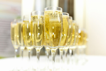 lot of blurred glasses with champagne on the reception party table on light background