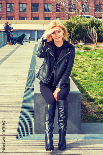 341c134eab3 Eastern European Woman wearing black leather jacket, long leather boots,  sitting by green lawn at street park in New York, raising hand to protect  eyes from ...