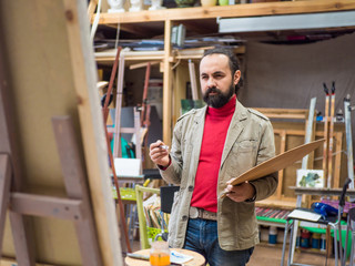 portrait of contemporary bearded artist looking at his panting on canvas deep in thought while working in art studio